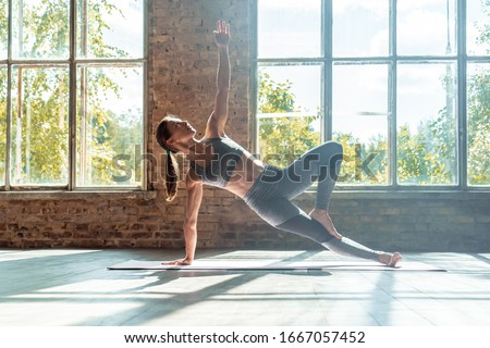 Young sporty fit woman trainer do practice individual hatha yoga instructor training Vasisthasana side plank,arm leg support balancing pose modern gym mat wooden floor window healthy lifestyle concept