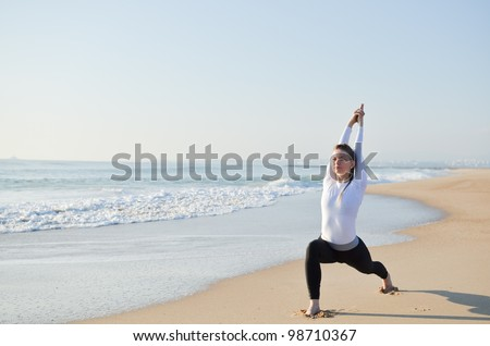 Young sporty girl doing exercise on the beach