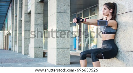 Young sporty girl doing wall sitting exercise urban outdoors. #696639526