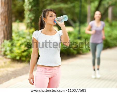 Young sporty girl drinking water outdoors