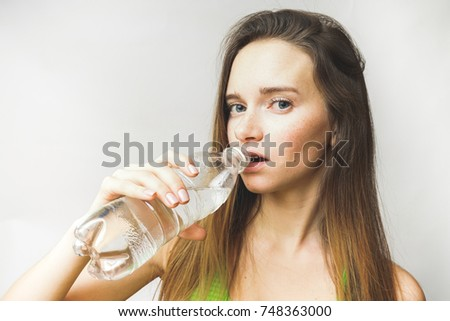 young sporty girl drinks clean water and looks at the camera