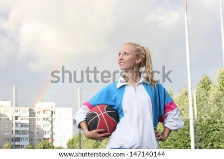 Young sporty girl holding basketball ball