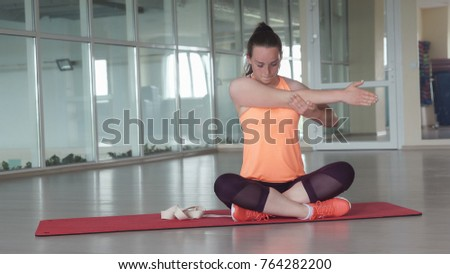 Young sporty girl in sports clothes doing warm-up on the rug in the gym with tape. #764282200