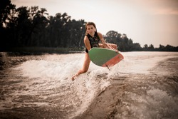 Young sporty girl in swimsuit wakesurifing and flying in the river near forest