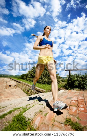 Young sporty girl running on stairs, outdoor - stock photo