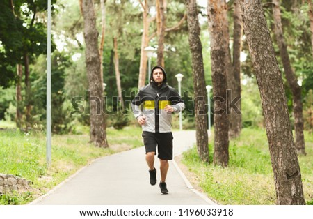 Young sporty guy in windbreaker jogging on valley in autumn park, training endurance for marathon
