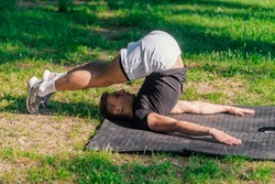 Young sporty handsome man practicing yoga in the park and doing the plow pose.