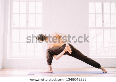 Young sporty man doing yoga in studio, with wooden floor and big windows. Freedom, health and yoga concept.