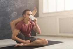 Young sporty man in flexible yoga pose drinking tea, sitting on mat at gym and practicing twisting exercise, copy space