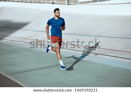 Young sporty man in sportswear shorts and t-shirt training in city