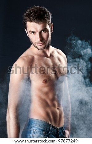 young sporty man over Smoke. Muscles, a close up