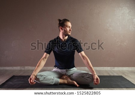 Young sporty man practicing yoga, meditating in Half Lotus pose, working out, wearing sportswear, indoor full length, gray yoga studio