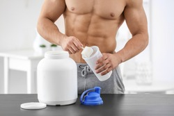 Young sporty man preparing protein shake at table