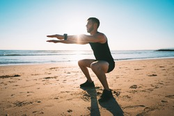 Young sporty man squatting or exercising on the beach during sunset. Athletic man doing fitness workout or training outdoors. Sports and healthy lifestyle