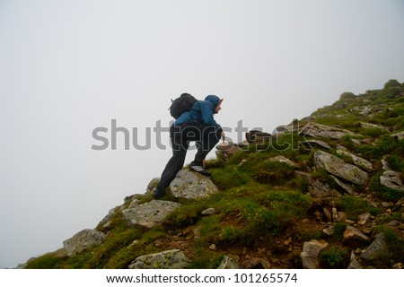 Young sporty man with backpack walking through rocky land to the top a mountain
