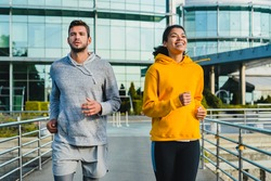 Young sporty mixed race couple running together against modern building made of glass