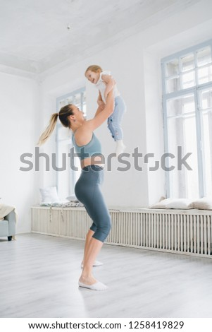 Young sporty mother and baby girl do exercises together in the gym. Parent and child healthy development, fitness and relaxation. Healthy lifestyle concept photo. Toning.