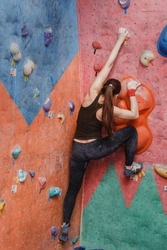 Young sporty muscular woman climbing up on rock wall in gym, rear view. Concept of professional bouldering