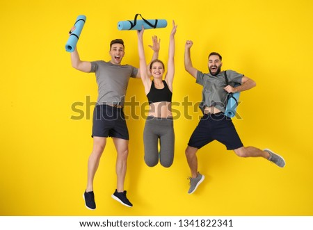 Young sporty people jumping against color background