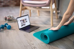 Young sporty slim woman preparing for online fitness training with modern laptop. Healthy lifestyle concept, online fitness and sport lessons.