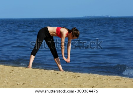 Young sporty woman doing exercise on beach #300384476