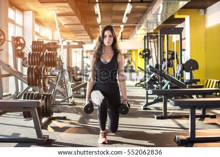 Stock Photo Young sporty woman doing exercises with weights in gym.
