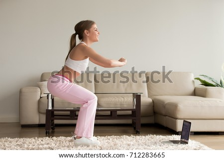 Young sporty woman doing two-leg deep squat morning exercise standing in living room, teen girl burning fat calories with online fitness training help crouching for buttocks lift at home, side view
