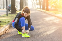 Young Sporty Woman Doing Up her Shoes Before Running. She wears Glow Yellow Shoes. The Girl is Crouched on Footpath, Backlight Setting.