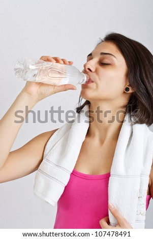 Young sporty woman drinking water on grey background