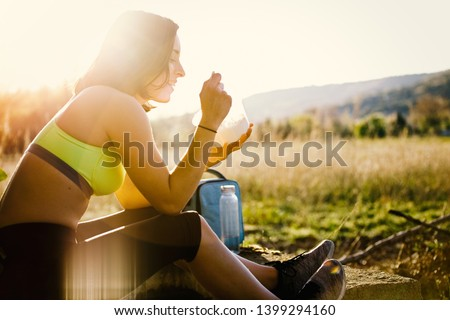 Young sporty woman eating healthy lunch in the field at the sunset