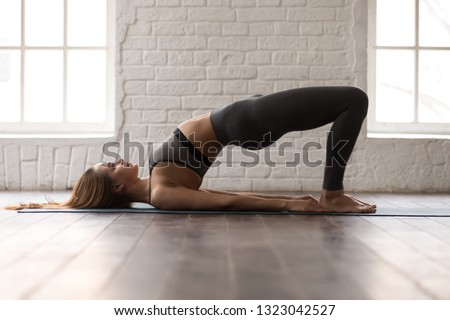 Young sporty woman in grey sportswear, leggings and bra practicing yoga, beautiful girl doing Glute Bridge exercise, dvi pada pithasana pose, working out at home or in yoga studio
