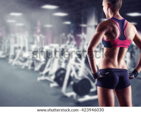 Young sporty woman in the gym. Back view