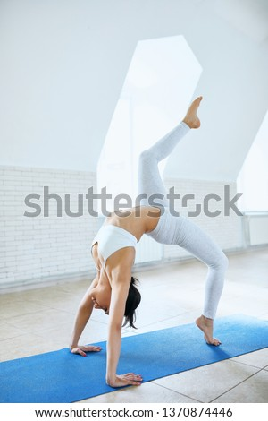 young sporty woman in white sportswear practicing yoga, stretching exercise in yoga studio with white wall background. Athletic lady standing in One legged Wheel pose, Bridge pose, working out