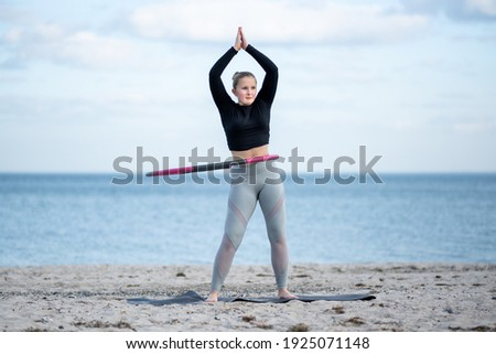 Young sporty woman is exercising with Hula hoop outdoors at the beach for healthy lifestyle concept. Stock photo ©