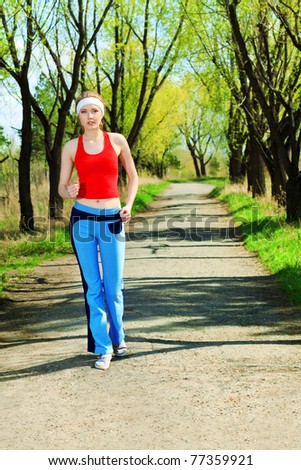 Young sporty woman is jogging outdoor.