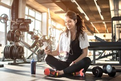 Young sporty woman listening to music on smartphone in gym. Break after hard workout.