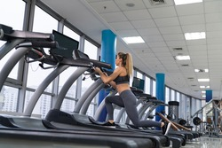 Young sporty Woman On Running Machine In Gym
