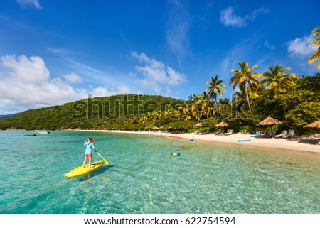 Young sporty woman on tropical beach vacation paddling on stand up board
