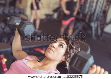 Young sporty woman portrait working out in the gym with dumbbel. Concept of active lifestyle. #1183235575