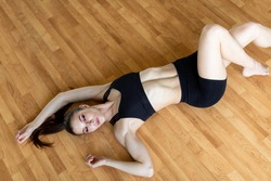 Young sporty woman practicing, doing crisscross exercise, bicycle crunches pose, working out, wearing sportswear, black pants and top, indoor full length