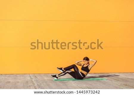 Young sporty woman practicing, doing crisscross exercise, bicycle crunches pose, working out, wearing sportswear, black pants and top. Outdoor, orange wall background, sport and healthy concept