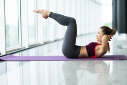 Young sporty woman practicing in gym, doing crisscross exercise, bicycle crunches pose near window at gym