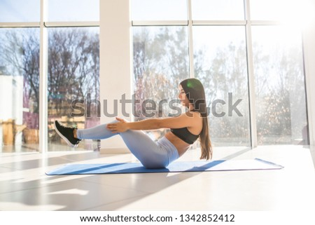 Young sporty woman practicing in gym, doing crisscross exercise, crunches pose, working out, wearing sportswear indoor in yoga or fitness club