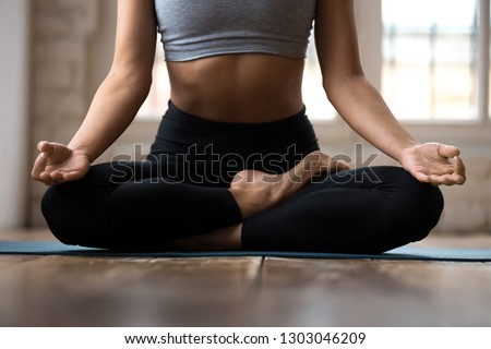 Young sporty woman practicing yoga, doing Ardha Padmasana exercise, Half Lotus pose with mudra gesture, working out, wearing sportswear, indoor close up, white yoga studio. Well-being concept