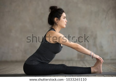 Young sporty woman practicing yoga, doing paschimottanasana exercise, Seated forward bend pose, working out, wearing sportswear, black pants and top, indoor full length, gray wall in yoga studio #1033265110