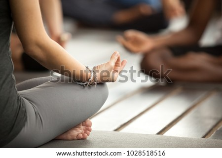 Young sporty woman practicing yoga lesson sitting in Sukhasana exercise, Easy Seat pose with mudra gesture, working out, female arms with wrist bracelets close up, studio