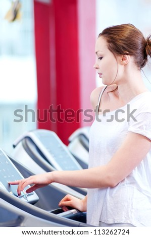 Young sporty woman run on machine in the gym centre