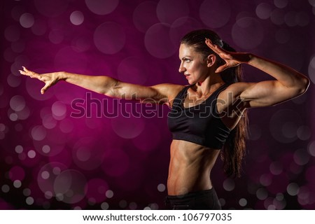 Young sporty woman shows a hand forward. The background bokeh