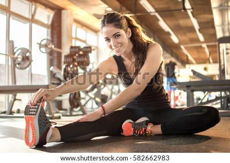 Young sporty woman stretching at gym.