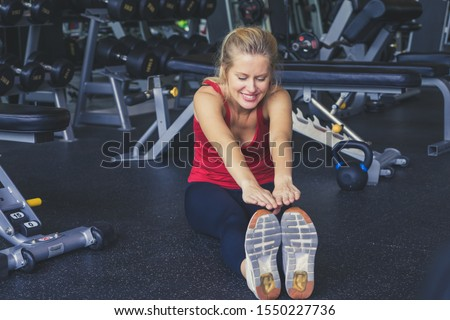 Young sporty woman stretching at gym.Fit Caucasian woman stretching her leg to warm up.sexy women stretch before exercising.Concept of exercise in gym fitness.